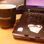Min dator med GNU-klistermärke och en Microsoft-mugg